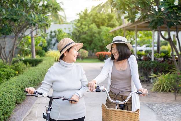 Happy senior asian women cycling bicycle with daughter at public park