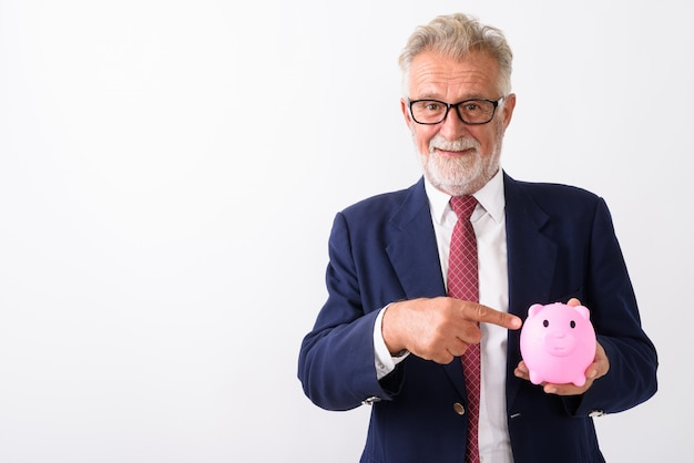 Happy senior bearded businessman smiling while pointing at piggy bank on white
