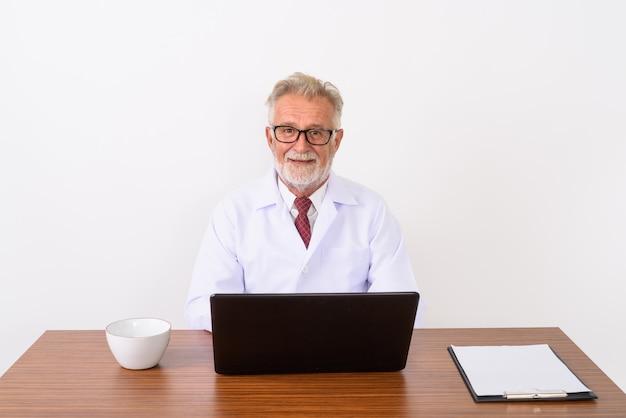 Счастливый старший бородатый мужчина доктор улыбается и сидит на деревянном столе с ноутбуком на белом