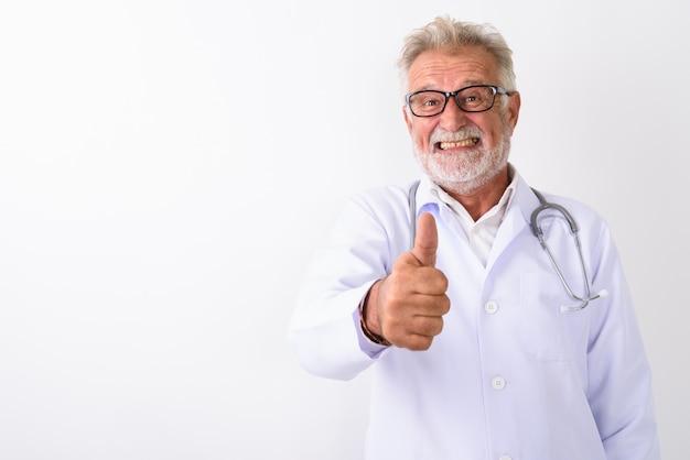 Счастливый старший бородатый мужчина доктор улыбается, давая большой палец вверх на белом