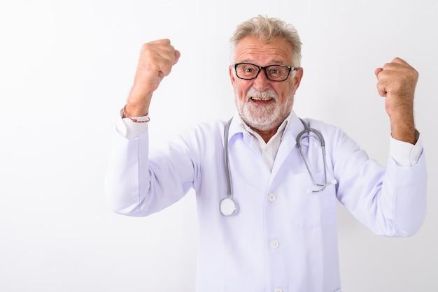 Счастливый старший бородатый мужчина доктор улыбается, глядя возбужденным на белом