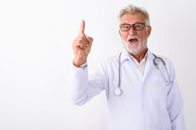 Счастливый старший бородатый мужчина доктор улыбается, указывая пальцем на белом