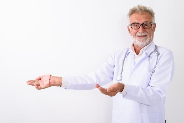 Счастливый старший бородатый мужчина доктор улыбается, показывая что-то на белом
