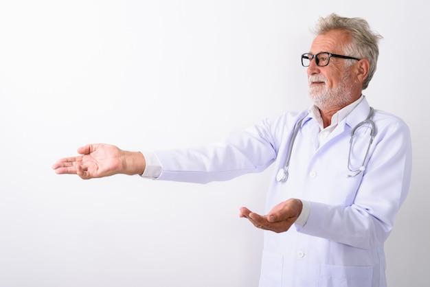 Счастливый старший бородатый мужчина доктор улыбается, показывая что-то в сторону на белом