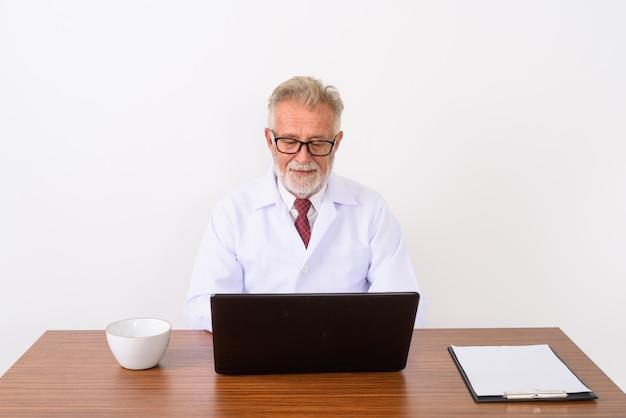 Счастливый старший бородатый мужчина врач улыбается при использовании ноутбука с чашкой кофе и буфером обмена на деревянном столе на белом