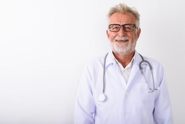 Счастливый старший бородатый мужчина врач улыбается в очках на белом