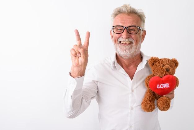 Счастливый старший бородатый мужчина улыбается и дает знак мира, держа плюшевого мишку с сердцем и знаком любви, в очках на белом.