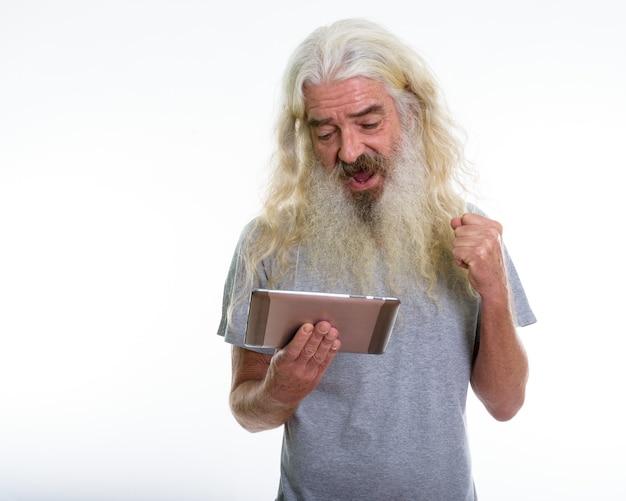 笑顔でタブレットを見て幸せなシニアひげを生やした男