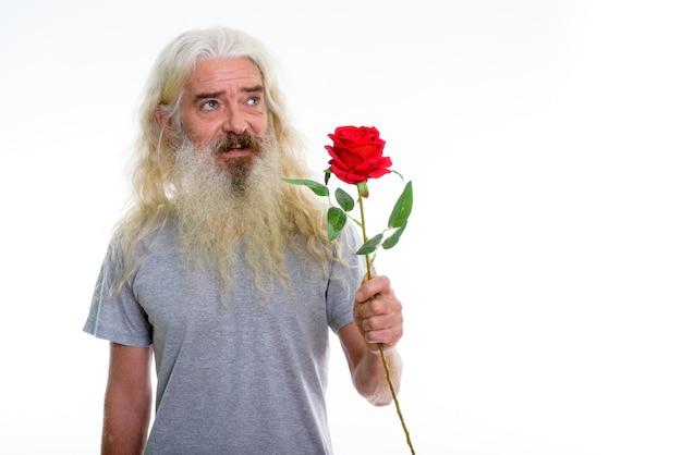 Счастливый старший бородатый мужчина улыбается и думает, держа красную розу