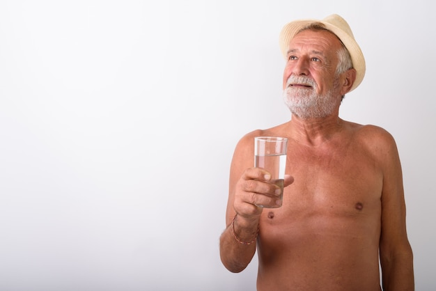 Happy senior bearded man smiling and thinking while holding glass of water with hat shirtless on white