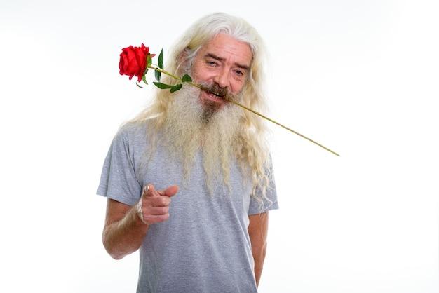 Счастливый старший бородатый мужчина улыбается, кусая красную розу