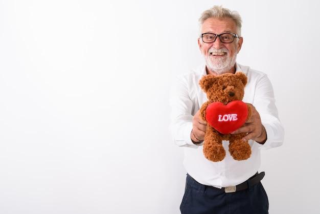 Счастливый старший бородатый мужчина улыбается, давая плюшевого мишку с сердцем и знаком любви, в очках на белом