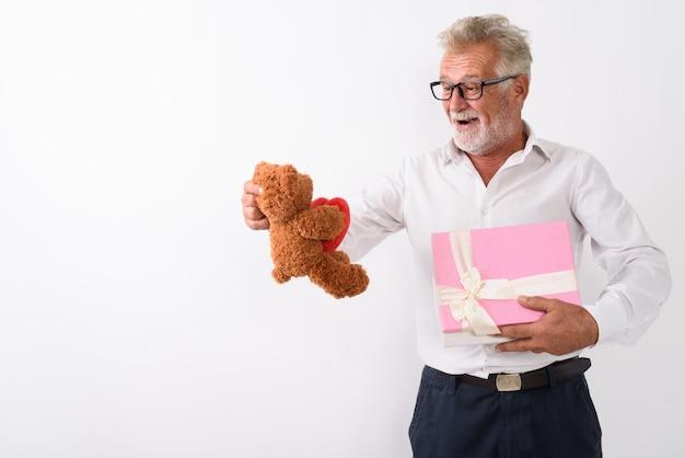 Счастливый старший бородатый мужчина улыбается, держа подарочную коробку и глядя на плюшевого мишку с сердцем и знаком любви, нося очки на белом.
