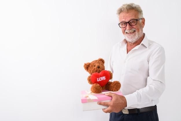 Счастливый старший бородатый мужчина улыбается, держа подарочную коробку и плюшевого мишку с сердцем и знаком любви сверху на белом