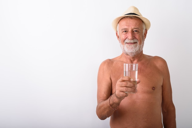 Happy senior bearded man smiling while holding glass of water and wearing hat shirtless on white