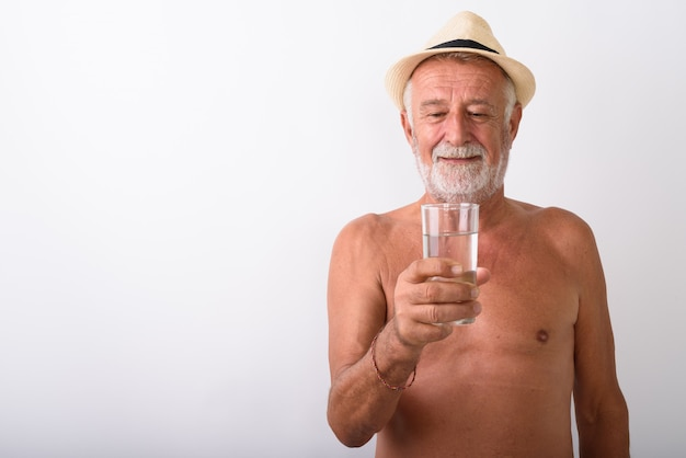 Happy senior bearded man smiling while looking at glass of water and wearing hat shirtless on white