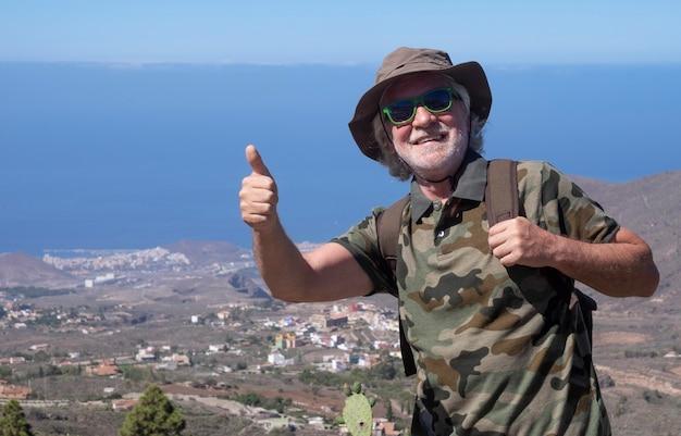 모자와 배낭을 메고 테네리페의 산 풍경을 여행하며 자유와 휴가를 즐기고 있는 행복한 노인 - 바다 너머 지평선 - 활동적인 은퇴한 노인과 재미있는 개념