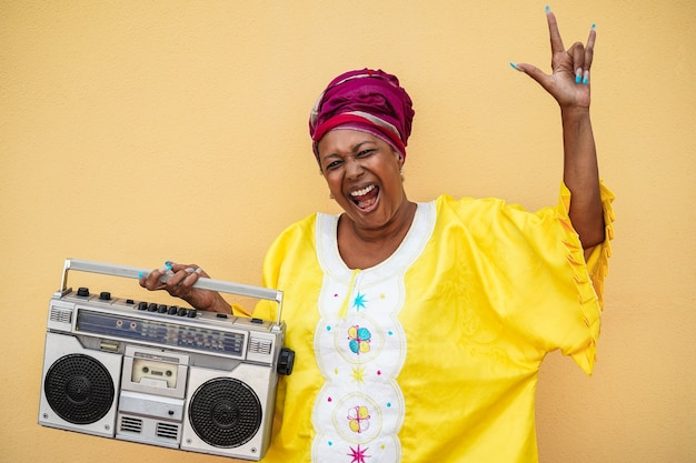 Happy senior black woman with traditional african dress dancing holding boombox stereo - focus on face