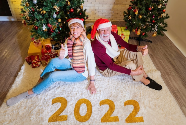 Happy senior caucasian couple celebrate christmas and 2022 new year together and thumb up with presents and decorated christmas tree and 2022 number decorated on fur mat in living room at home.