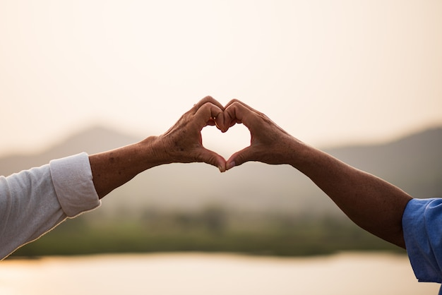 A happy senior couple asian old man and woman showing heart sign