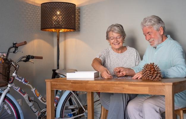 家で幸せな年配のカップルは、木製のテーブルでパズルをやって一緒に時間を過ごします。