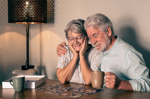 Счастливая пара старших дома проводить время вместе, решая головоломку на деревянном столе.