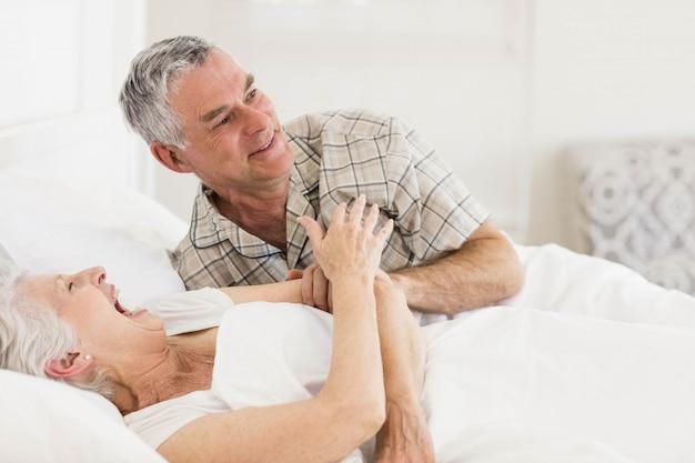 Happy senior couple at bed at home