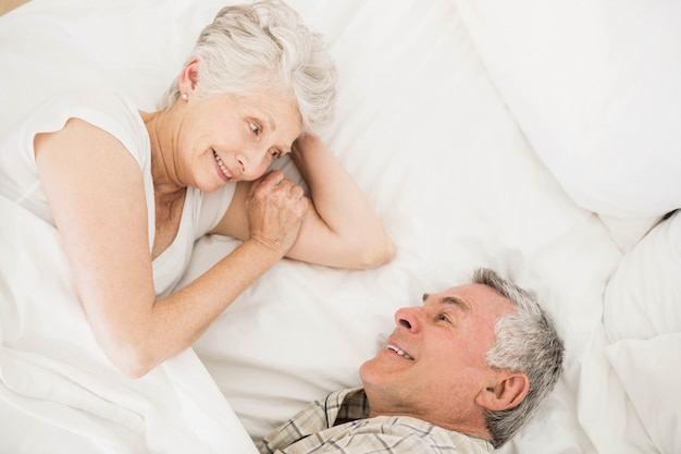 Happy senior couple on bed talking