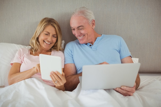 Happy senior couple on bed using laptop and digital tablet