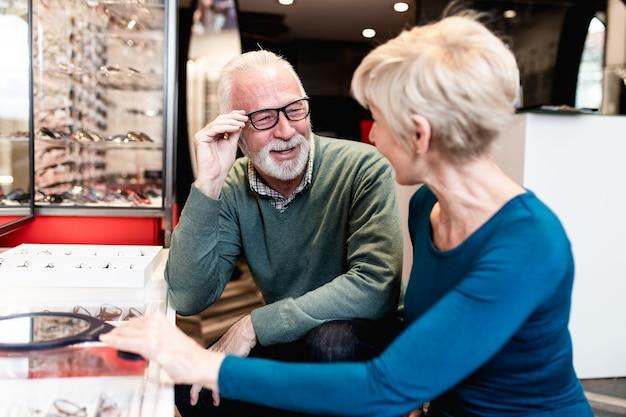 光学店で一緒に眼鏡フレームを選ぶ幸せな年配のカップル。