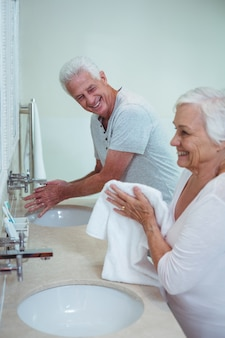 Happy senior couple cleaning hands in bathroom