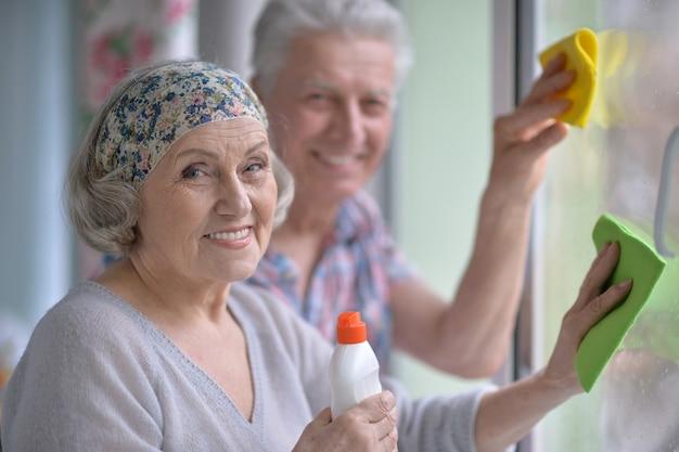 幸せな年配のカップルが家で窓を掃除する