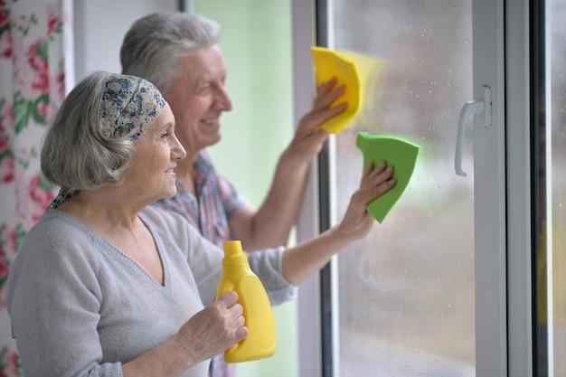 幸せな年配のカップルが家で窓を掃除