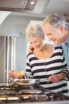 Happy senior couple cooking food
