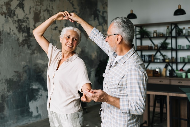 Happy senior couple dancing in the home