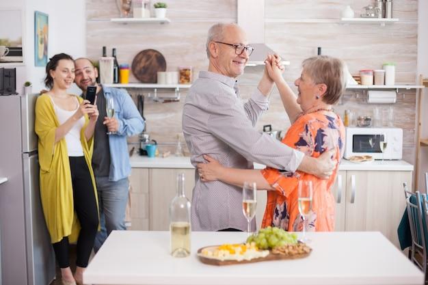 家族のお祝いの間にキッチンで踊る幸せな年配のカップル。木の板に美味しいチーズ盛り合わせ。写真を撮る女性。