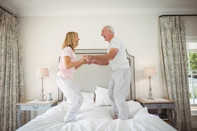 Счастливая пара старших танцует на кровати