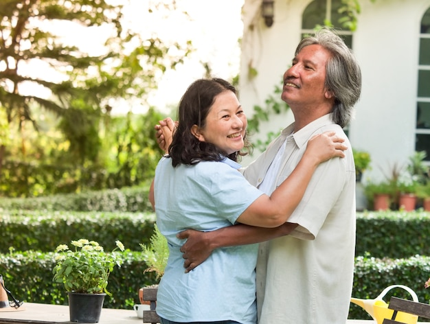 Happy senior couple dancing together in garden home.
