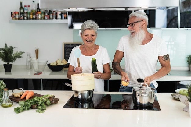Happy senior couple dancing while cooking together at home - focus on faces