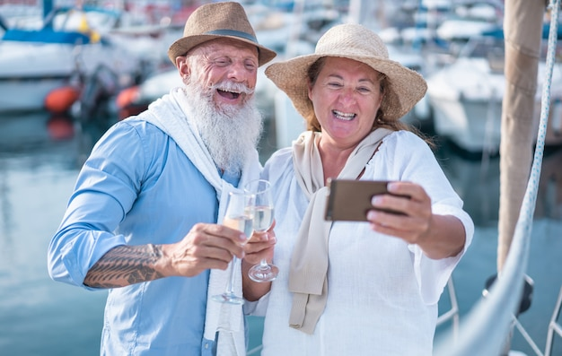 Happy senior couple doing selfie, cheering with champagne on a sailboat during anniversary vacation