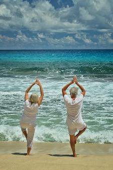 Happy senior couple doing yoga exercising in summer on  seashore