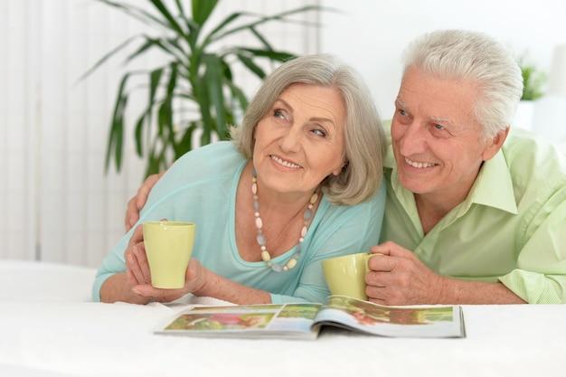 차를 마시고 잡지를 읽는 행복한 시니어 커플