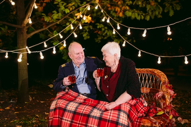 Happy senior couple drinking tea in the evening sitting on the couch.