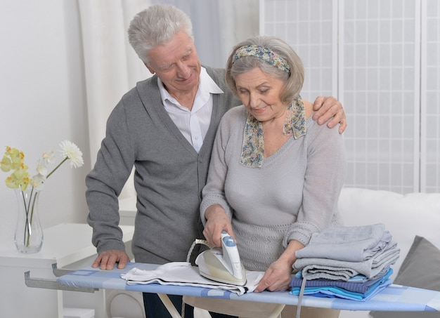 自宅でアイロンをかけている間の幸せな年配のカップル