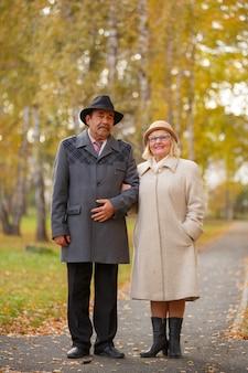 Счастливая пара старших, охватывающей в парке осенью