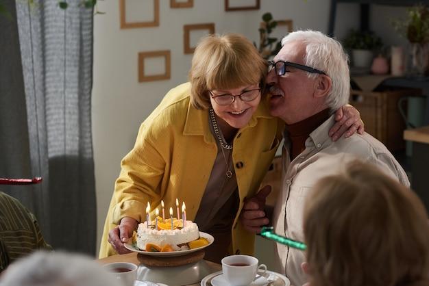 自宅でケーキで記念日を祝いながらテーブルで抱きしめる幸せな年配のカップル