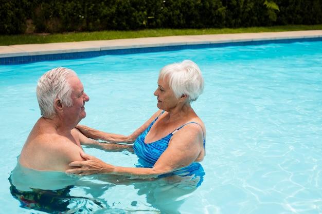 수영장에서 서로 껴 안은 행복 한 노인 부부