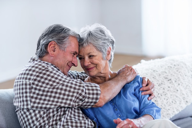 Happy senior couple embracing each other on sofa