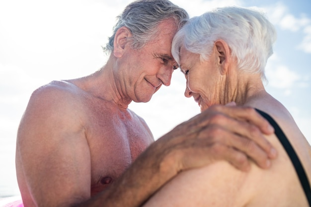 Happy senior couple embracing face to face on the beach