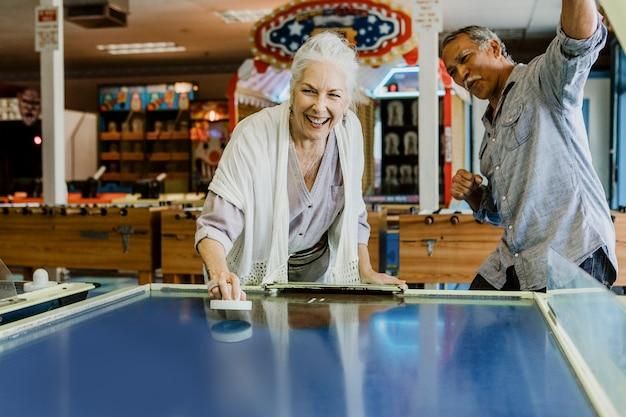 ゲームアーケード内でテーブルホッケーのゲームを楽しんで幸せな年配のカップル